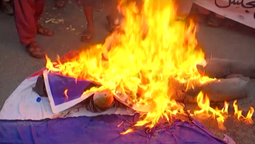Pakistani protesters burn effigy of Macron and French flag.